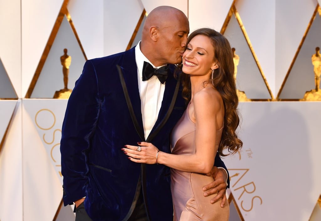 Dwayne Johnson is usually pretty private about his romance with longtime partner Lauren Hashian, but it seems he's getting more comfortable about showing PDA. On Sunday, the duo were all over each other when they hit the red carpet at Sunday's Oscars. In addition to wrapping his arm around Lauren's waist, Dwayne showered his girlfriend with several kisses on the cheek. Now if only we were so lucky.