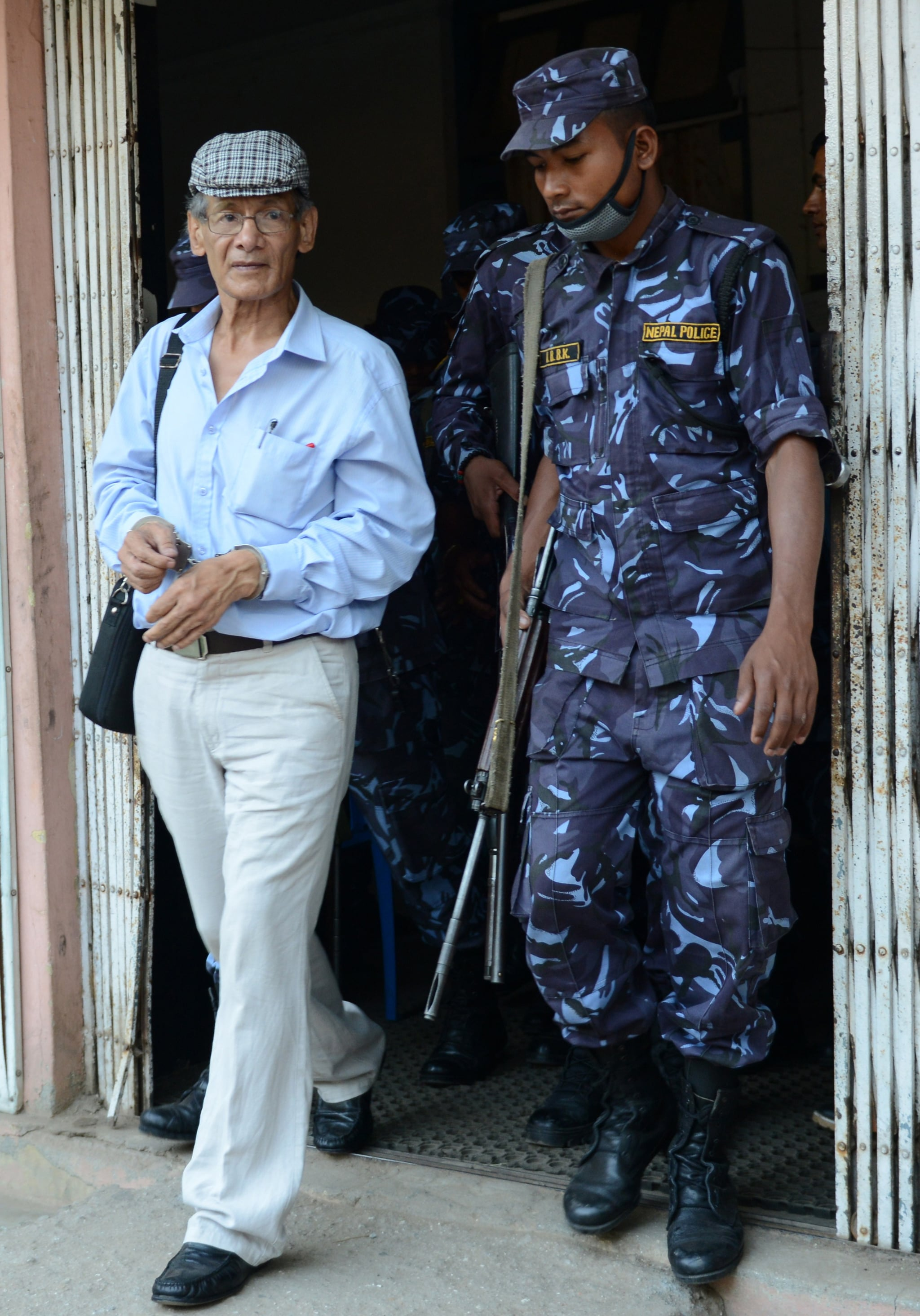 French serial killer Charles Sobhraj (L) is escorted by Nepalese police to a waiting vehicle after a hearing at a district court on a case related to the murder of Canadian backpacker Laurent Ormond Carriere, in Bhaktapur on June 12, 2014. Sobhraj, a French citizen who is serving a life sentence in Nepal for the murder of an American backbacker in 1975, has been linked with a string of killings across Asia in the 1970s, earning the nickname