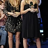 Twinning combo: Mary-Kate and Ashley visited the Toronto MuchMusic Studios in 2006 showcasing their knack for creating effortlessly chic ensembles.  Mary-Kate complemented her metallic-brushed mini with dual-strap sandals and a few statement rings. Ashley took her LBD to new heights via stacks of necklaces, bracelets, and red-hot peep-toes.