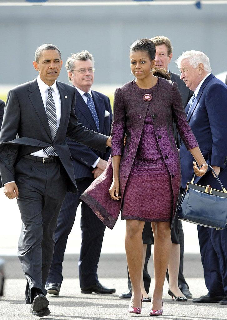 Leaving London, Michelle chose a purple ombré Peter Som dress and coat.
