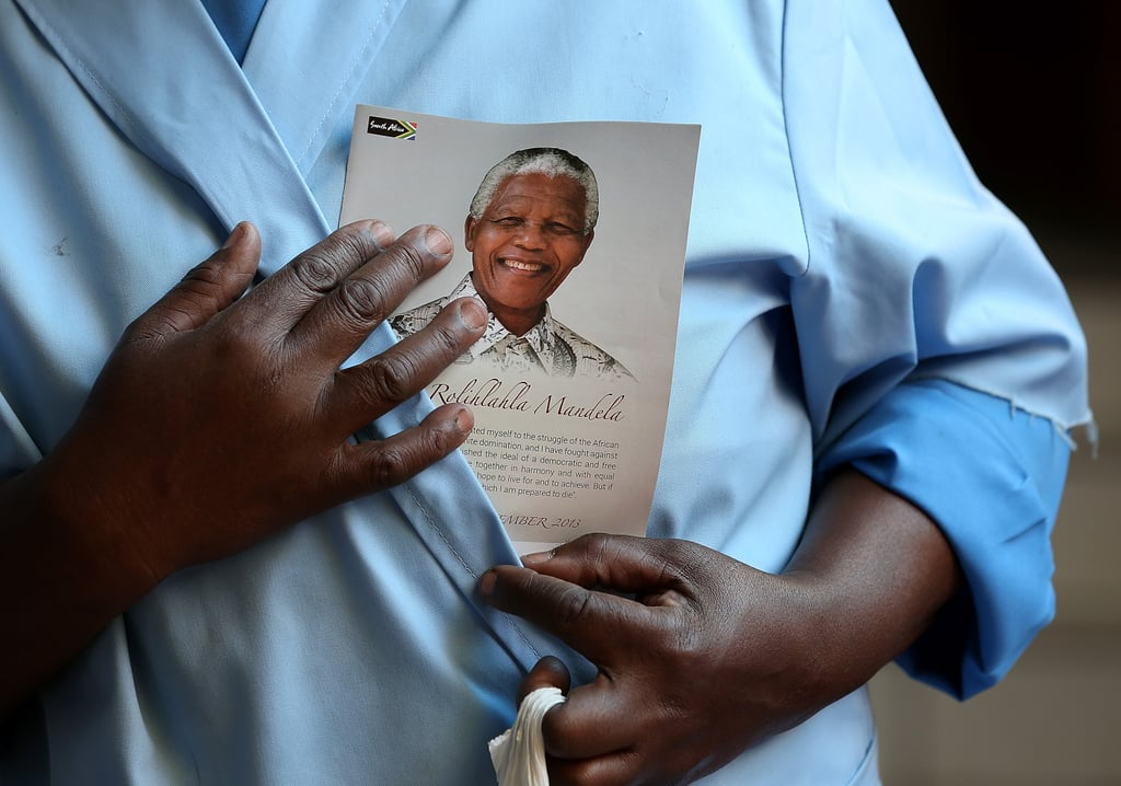 A women held up a pamphlet featuring Nelson Mandela during a church service in Soweta, South Africa.