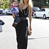 Rachel Zoe stayed chic while toting baby Skyler in a black maxi dress cinched at the waist and topped with a wide-brimmed straw hat.