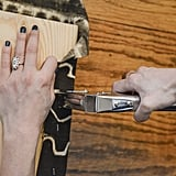 """Use your staple gun to secure the fabric on one side, stapling about an inch from the edge of the bench and spacing the staples about 1"""" apart."""