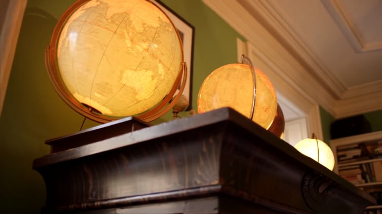 Topping a shelf in the study are some of her favorite pieces in the home, like these golden globes. Even though she's a Manhattan girl at heart, she loves to see and travel the world. This also gives you a better glance at the intimate details of the home including the tray ceilings.
