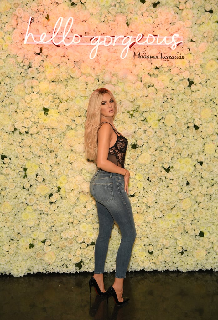 "Khloé Kardashian might have just gotten the coolest birthday present ever! That might be a bit dramatic, but a wax figure is pretty cool, right? The 34-year-old star's first-ever Madame Tussauds figure was unveiled at the Las Vegas location and the resemblance is striking. Her figure is posing in front of a flower wall with a neon pink ""Hello Gorgeous"" sign — it's similar to the wall Khloé had at her baby shower. Donning Good American high-waisted jeans, a sexy black lace bodysuit and Christian Louboutin pumps, Khloe's wax figure is wearing almost an exact copy of the outfit she wore to her Good American launch in 2016. All of the pieces were donated by Khloé herself and she worked closely with Madame Tussauds in the creation process, according to a press release. Keep scrolling to see the wax figure and compare just how much it looks like Khloé."