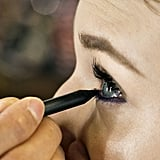 "To create a plum smoky eye, waterline of the bottom lashes at the root and just under the lashes with a deep violet liner — Jennings used MAC Pro's Longwear Eyeliner in Snow Shadow ($20). ""You want it to show up and be smoky,"" Jennings says. ""Make sure there are no spaces or gaps so you don't see any light spots on the eye."""