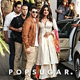 While heading to Jodhpur, India, for their wedding, Priyanka opted for a white kurta and a colorful dupatta. Nick kept it casual in a brown leather jacket, white shirt, khakis and Westward Leaning sunglasses.