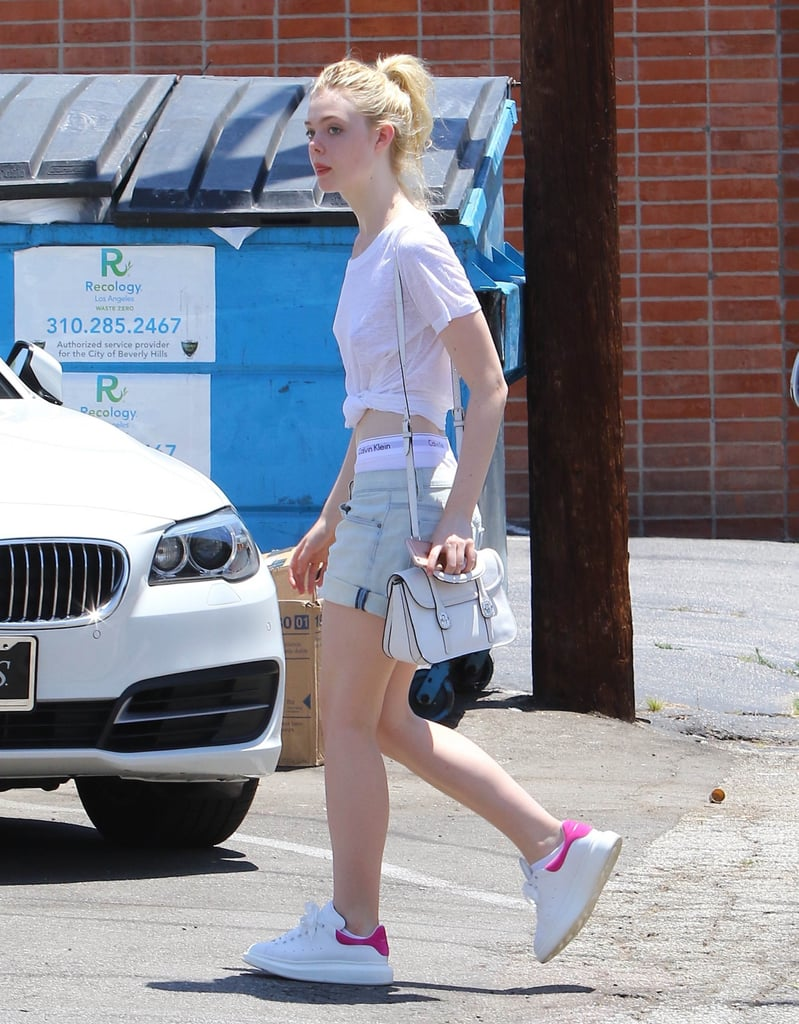 Elle let her Calvins peek out from the waistband of her cutoffs, tying up her white t-shirt into a crop top.