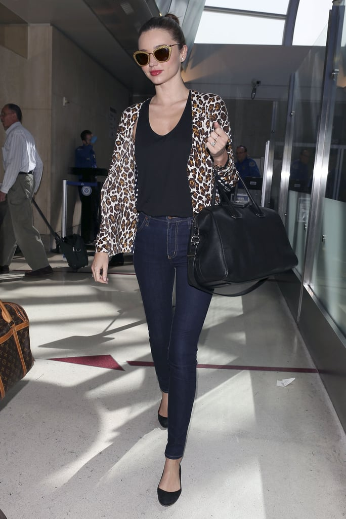 leopard Stella McCartney cardigan ($1,128), glitter Miu Miu shades ($390), and her trusty Givenchy tote after touching down at LAX.