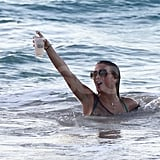 Julianne Hough held her drink up while swimming to a boat.