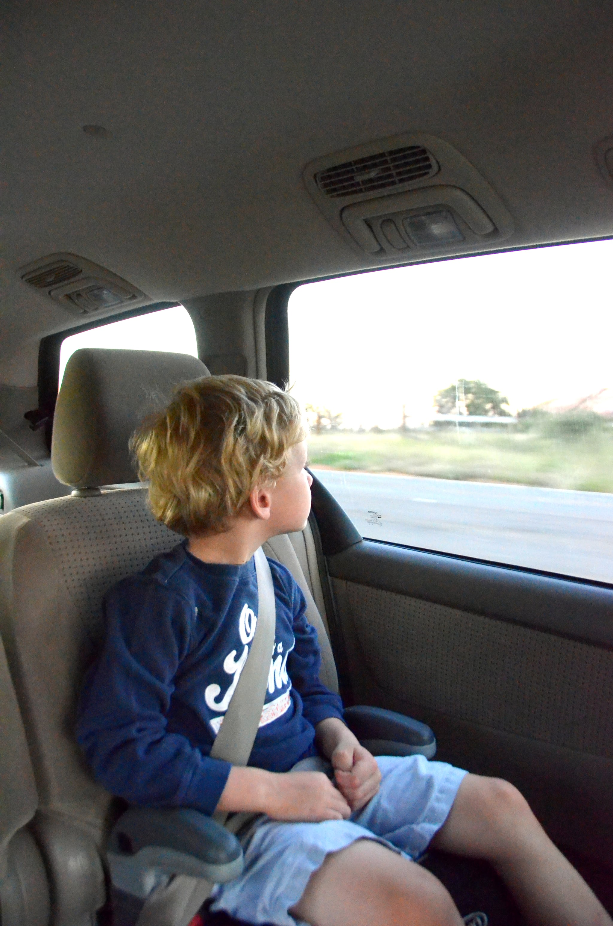 A young boy sits in a booster seat looking out the window of a moving vehicle.