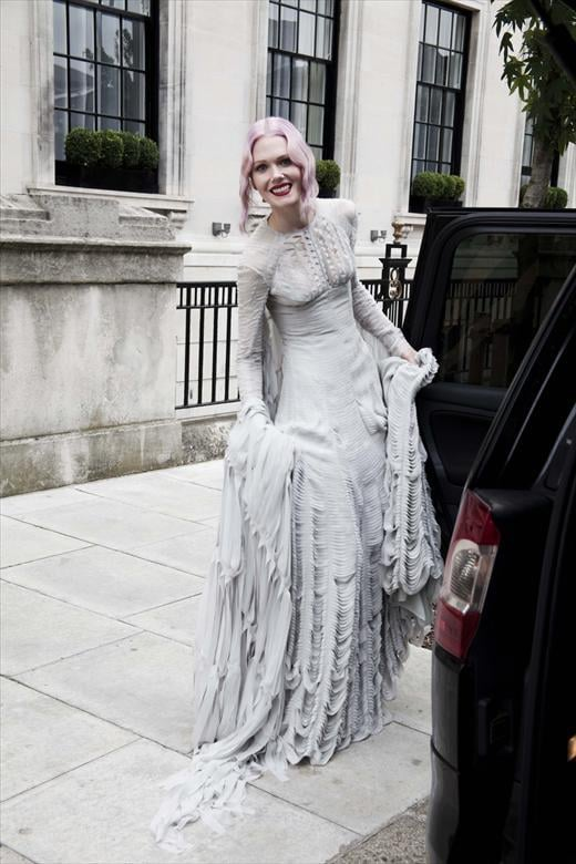 >> Gareth Pugh doesn't currently participate in couture, but he recently took a crack at a showstopping bridal gown — for his best friend and longtime collaborator, stylist Katie Shillingford, who was married last Friday. Shillingford wed Alex Dromgoole in the 1930s Art Deco-style Eltham Palace of Greenwich, England, wearing a custom pale  grey slashed chiffon Pugh dress, complete with a trail that hung from her  shoulders and a veil created by Stephen Jones. Shillingford's bridesmaids — including Dazed & Confused and Another's Karen Langley, who helped design the wedding cake — wore black striped knitted dresses by Craig Lawrence, and Shillingford changed in a Fall 2011 Gareth Pugh gold dress and Fall 2011 Miu Miu shoes for the reception.