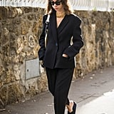 A Black Suit and Coordinating Black Slides Is Understated but Not Unnoticed