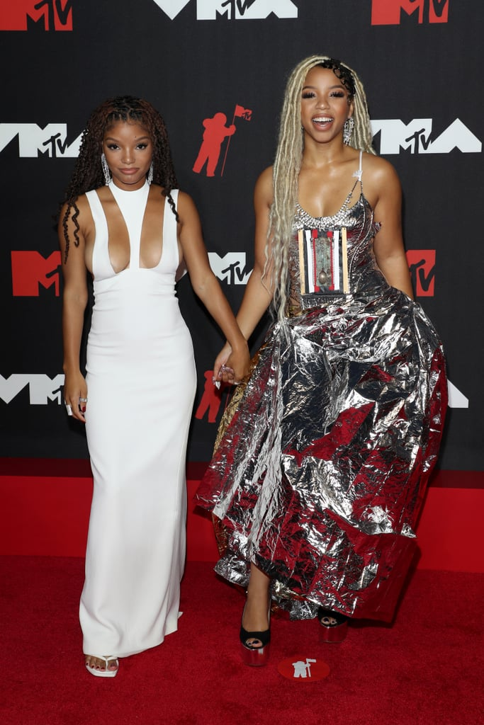 """Chloe and Halle Bailey showed off their sweet sisterly bond as they attended the MTV VMAs together on Sunday night. The duo looked stunning as they stepped out on the red carpet walking hand in hand. While Chloe wore a silver gown, Halle looked equally as beautiful in a white cutout dress. Though the sisters aren't performing together as Chloe x Halle during the show, we will get to see the debut of Chloe's solo career as she performs """"Have Mercy"""" for the first time ever. Of course, Halle will be presenting the performance like the proud sister she is. See more cute photos from their appearance ahead.       Related:                                                                                                           The MTV VMAs Red Carpet Is So Upbeat, the Fashion Alone Will Make You Get Up and Dance"""