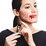"""For a real American Psycho flourish, splatter the blood with a stiff brush like Make Up For Ever Angled Artistic Brush 404 ($23). Dip the ends into """"blood,"""" and run your fingers over the bristles to get a random spray of red."""