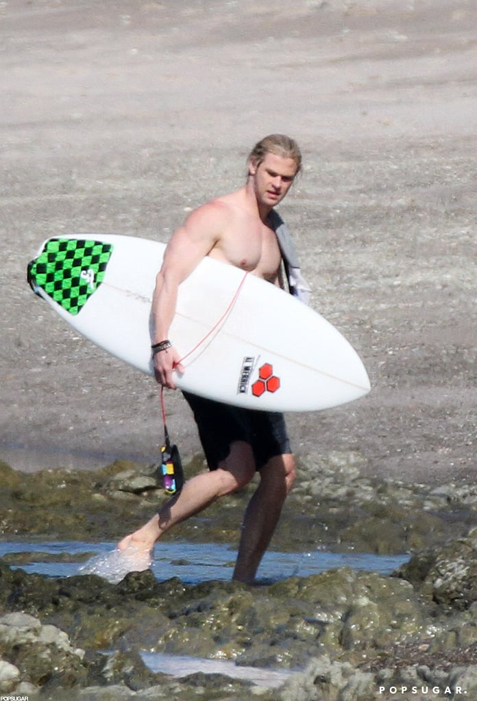 Shirtless Chris Hemsworth carried his surfboard.