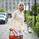 For a pop of colour, style a belted blazer with shorts and a bright orange Bottega bag.
