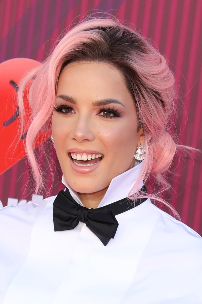 Whether she's bad at love is debatable, but Halsey is indisputably the queen of hair transformations, from platinum buzz cuts to her new cotton candy pink waves. The singer debuted her new color at the iHeartRadio Music Awards on March 14, wearing it in a loose bun for the red carpet and down for her performances. While the pink style is probably a wig (she was spotted recently with a magenta pixie), it looks so good on her, we think she should consider growing it out and making it this color in the long-term. Check out her look from all angles, ahead.