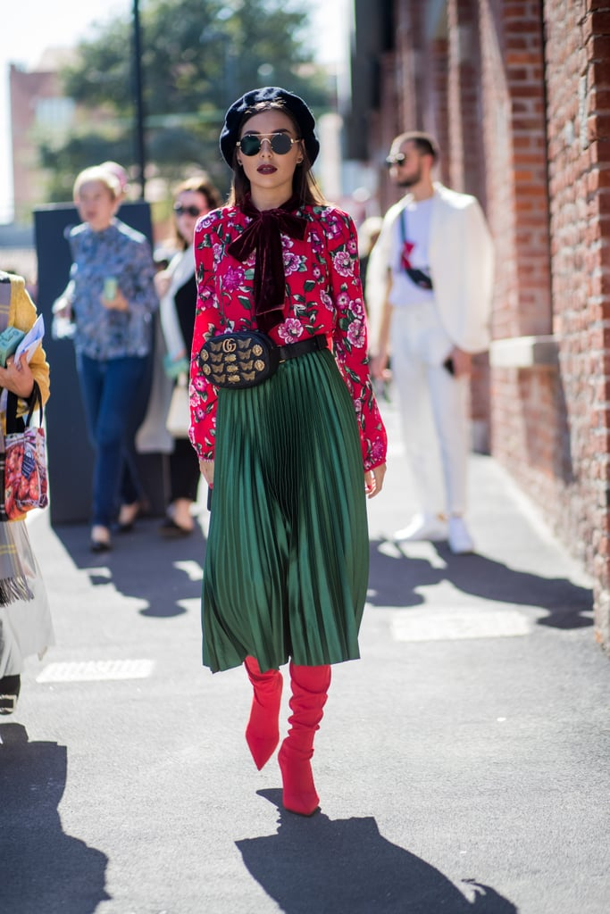 Style One With a Pleated Skirt, a Floral Blouse, and Red Boots