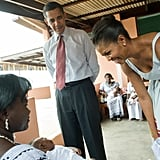 First Lady Michelle Obama smiled at a baby during a July 2009 hospital visit in Ghana.