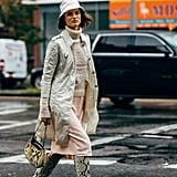 A neutral-colored bucket hat is just the icing on the cake when you're already sporting a multidimensional look consisting of snakeskin boots and an embellished purse.