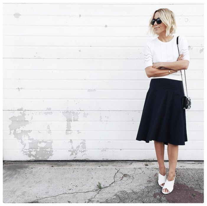 A White Sweater, Black Midi Skirt, and Slip-On Shoes