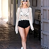 Lottie Moss wearing a crochet top, black denim shorts, and trainers at the festival.