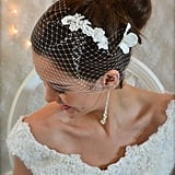 This comb ($32) has it all: lace, sheer sequins, and pearls. Wear it as is, wear with a satin ribbon, or use it over the comb of a birdcage veil.