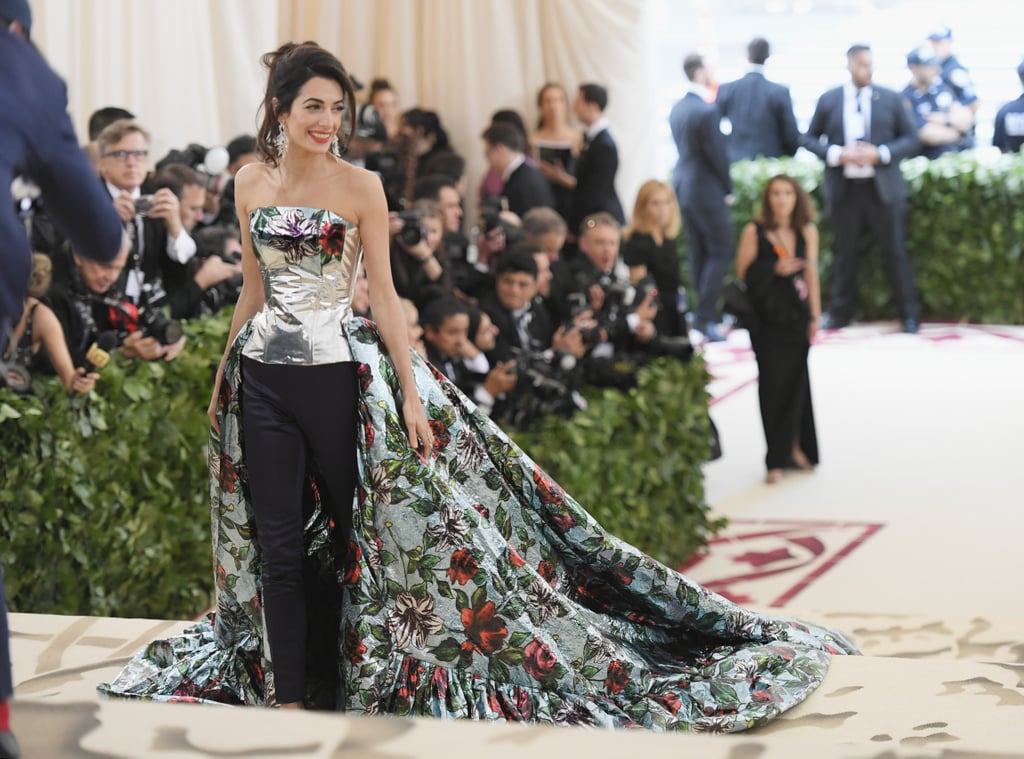 "As one of the cohosts for the 2018 Met Gala, Amal Clooney pulled up to the red carpet going in a direction she's never gone before: the ""pants gown."" Wearing a stunning ensemble by Richard Quinn, the mom of two illuminated floral and metallic excellence. Hubby George Clooney went for his classic black and white tuxedo look, ensuring all eyes were on his beautiful wife. From the front, it looks like Amal is wearing a floral bustier and navy pants, but from the back, her floral train looks entirely different. Read on to see the couple's stunning 2018 Met Gala appearance."