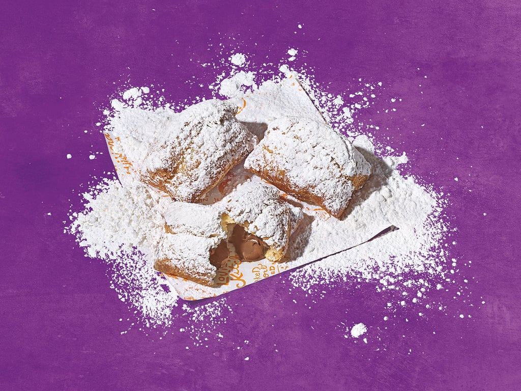 "Are y'all ready to have dust everywhere? Because we sure are! On Dec. 14, Popeyes announced that Chocolate Beignets are being added to menus nationwide, and we've got a full stack of napkins ready to go. As a New Orleans-style chain, Popeyes wanted to honor the great dessert that is beignets — but these aren't your typical fluffy, dusty treat. Popeyes Chocolate Beignets are filled with melted Hershey's chocolate and covered in powdered sugar. Drooling yet? The beignets are available in stores now for a limited time and are being sold in packs of three, six, and 12.  And because we know you're wondering, the oozing sweet is already getting great reviews on social media. One person who was lucky enough to try the beignets on the first day said they ""load it up with lots of powdered sugar."" Knowing how messy beignets can get, Popeyes hilariously released a ""Beignet Camo"" hoodie to mask ""the inevitable mess."" It's covered in splatter marks so we can really let loose while indulging and have no worries about making a mess. Check out how people are enjoying the new Popeyes Chocolate Beignets ahead and make sure to order some the next time you're out and about.      Related:                                                                                                           The 38 Easiest Christmas Cookies You Should Make This Year"