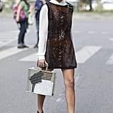 Bring your sleeveless dresses straight into early Fall by layering a top under it like this stylish showgoer.