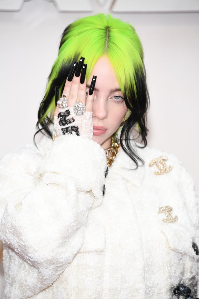"If you looked up ""effortlessly cool"" in the dictionary, you'd probably find a photo of Billie Eilish at the 2020 Oscars. On Sunday, the 18-year-old Grammy-winner made her debut at the Los Angeles ceremony looking chic in a white Chanel suit complete with her signature green hair. Even though Billie isn't nominated for any awards, it was still a big night for her, as she took the stage for a special in memoriam performance.  ""Honored to be performing during the in memoriam segment for the Oscars tonight covering a song I've always loved. Watch with us,"" Billie shared on her Instagram Stories before the show. It's still unclear what song Billie will be singing, but she did recently record the theme song for Daniel Craig's final James Bond film, No Time to Die, making her the youngest artist in history to write and record a theme song for the franchise. See more of Billie's night ahead!"
