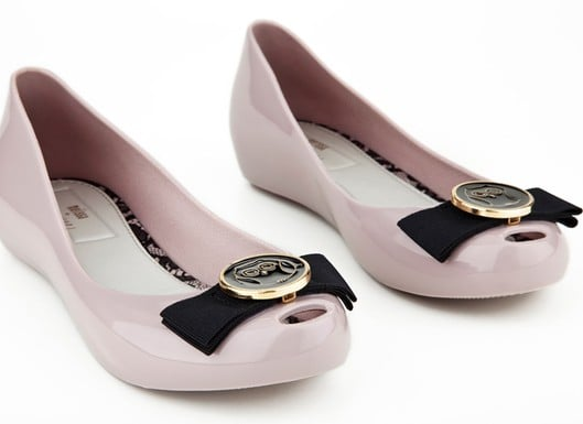""">> This upcoming Spring, Jason Wu and plastic shoe brand Melissa are teaming up to release two exclusive styles. Though both shoes are based on pre-existing Melissa bestsellers — the Ultragirl ballet flat and the Lady Dragon peep-toe slingback — they're injected with a strong dose of signature Wu: a Miss Wu owl logo bow tops the ballet flats, while a sunburst design culled directly from Wu's Fall 2011 collection adorns the pumps. """"It was really interesting for me to explore design possibilities with  plastic,"""" said Wu of the collaboration. """"I wanted to take advantage of the materials I was  given, make it all completely functional and waterproof and yet still  remain extremely sophisticated."""" Both styles will be available in black, burgundy, nude, and transparent gray, and also feature lining printed with pink and black lace. Wu is the first American designer to collaborate with Melissa; Vivienne Westwood, Gareth Pugh, and Jean Paul Gaultier have all previously partnered with the Brazillian shoe brand."""