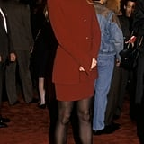 Nicole wearing a cranberry suit, tights, and pumps on the red carpet in 1992.