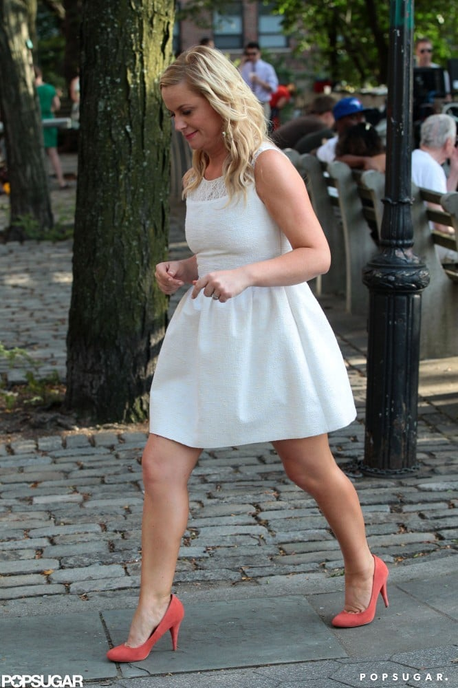 Amy Poehler paired pink shoes with her white dress.