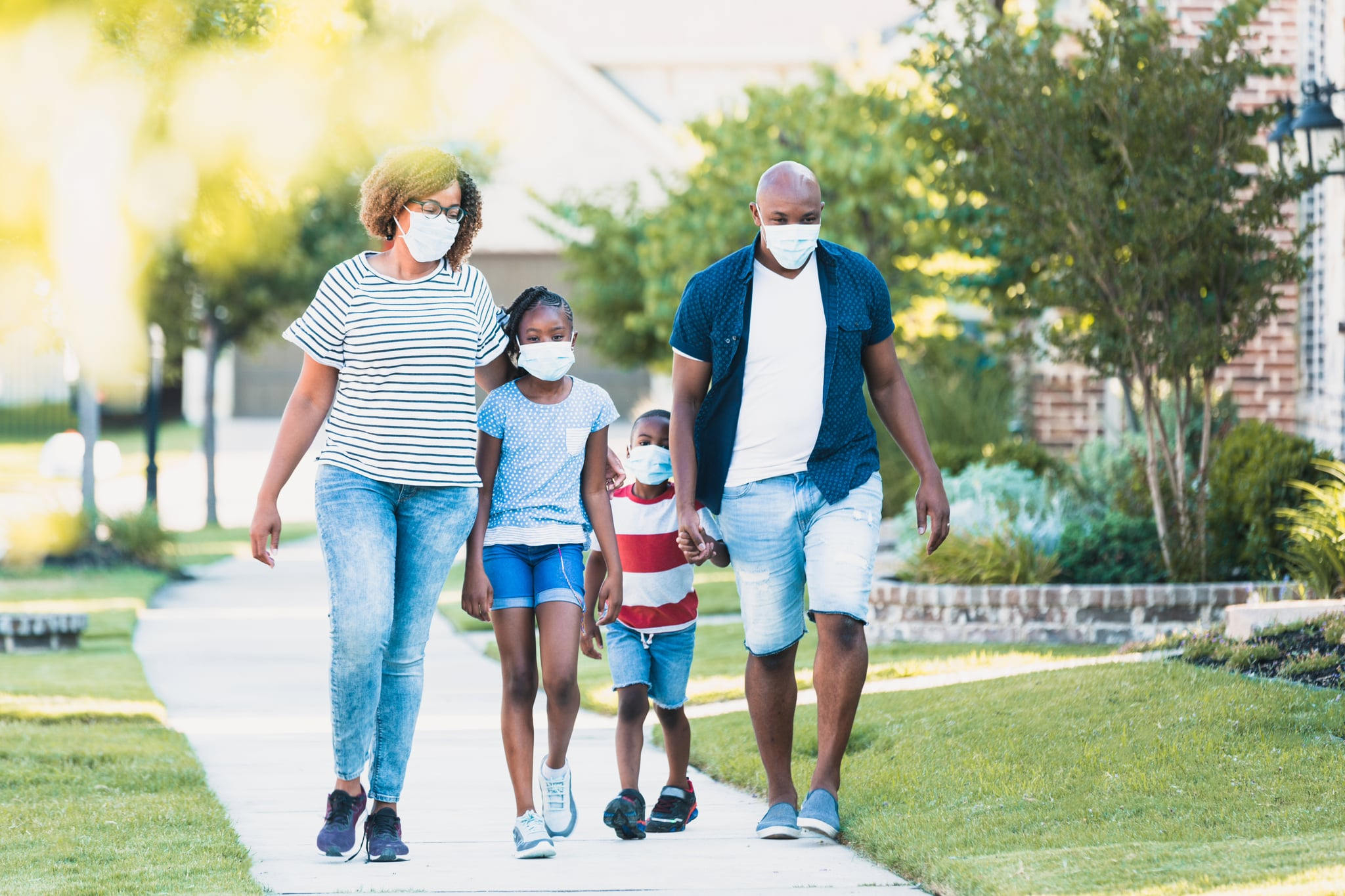A happy family wear face masks while walking in their neighbourhood during the COVID-19 pandemic.