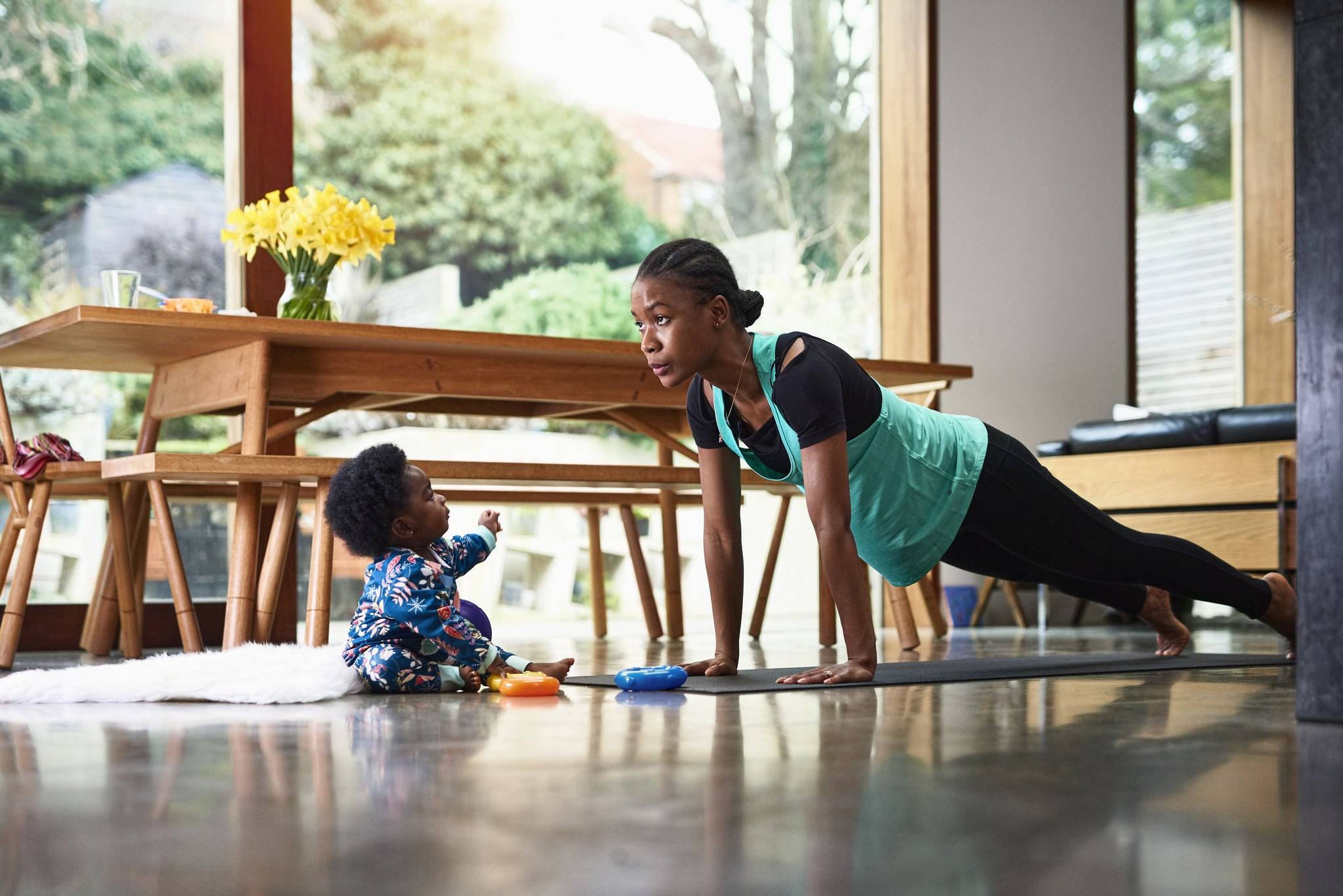 Baby boy (6-11 months) assisting mother performing yoga in livingroom