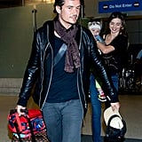 Miranda Kerr held Flynn Bloom as she arrived at LAX with husband Orlando Bloom.