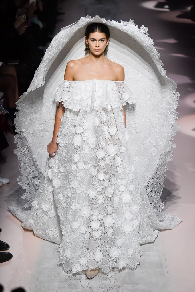 "Kaia Gerber owned the runway during Paris Fashion Week at Givenchy's Haute Couture Spring/Summer 2020 show in an elegant wedding gown eclipsed only by the massive dome-like veil that comes with it. Part of Clare Waight Keller's garden-inspired collection ""Une Lettre d'Amour,"" the romantic off-the-shoulder dress is layered with lace flowers of all shapes that creep onto the giant veil — so stunning! The veil itself is meant to replicate the silhouette of a bell, and I have to say the drama and scope of this look puts the Little Mermaid and her giant clam shell to shame. The exaggerated veil adds intrigue to the outfit, while also giving off an air of ""stay the f*ck away from my wedding dress,"" and we are so on board. Keep scrolling to take a closer look at the floral gown and veil ahead.       Related:                                                                                                           Sheesh! The Outfits at Men's Fashion Week in Paris Are Seriously Inspiring"