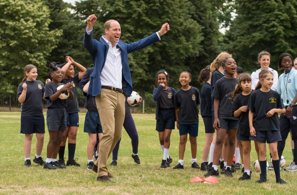 Prince William has been having a great July so far. After bonding with WWII veterans earlier this week, the famous royal took to the field on Thursday to play soccer with England's women's national football team, the Lionesses, and a group of young girls from the Wildcats Girl's Football program in London. While his khaki slacks, button-down shirt, and blue blazer weren't exactly athletic attire, that didn't stop him from getting into the game as he blocked the ball at the net. Plus, he looked ridiculously adorable as he celebrated scoring a goal. What can we say? Prince William is definitely a sporty spice.