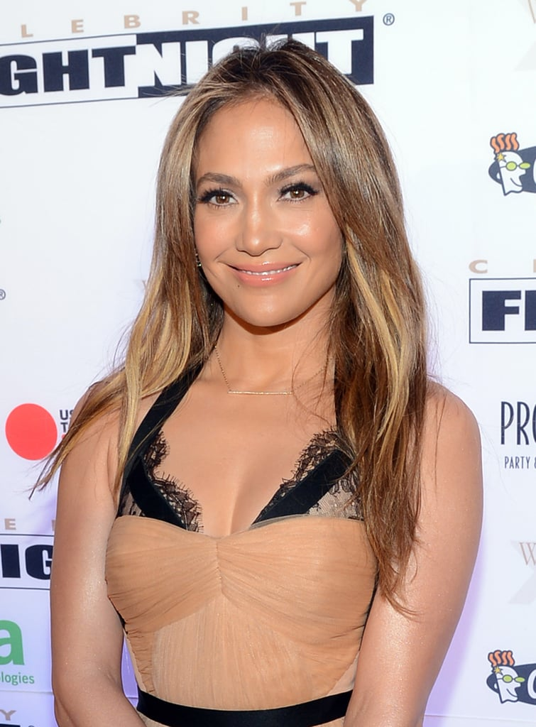Jennifer Lopez arrived at Celebrity Fight Night XIX in a peachy nude dress with black trim, which translated to her makeup look. She wore a peach hue on her lips and cheeks, finishing the style with black eyeliner and plenty of black mascara.
