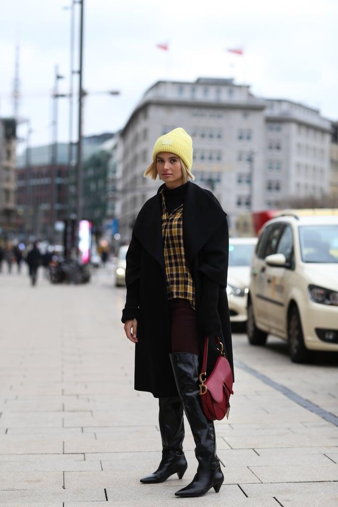 احمي نفسكِ من البرد بقبّعة صوفيّة صفراء، وقميص متصالب النقشات، وبنطال جينز ضيّق