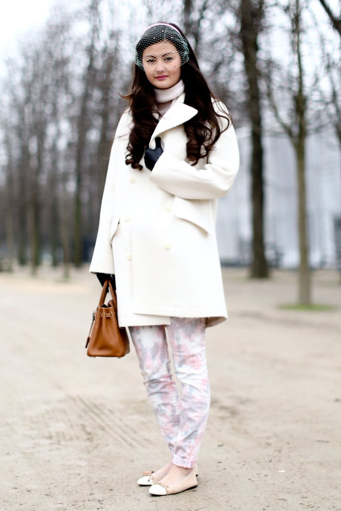 Sweet, soft florals and a creamy white coat play into the ladylike feel of her delicate veil.
