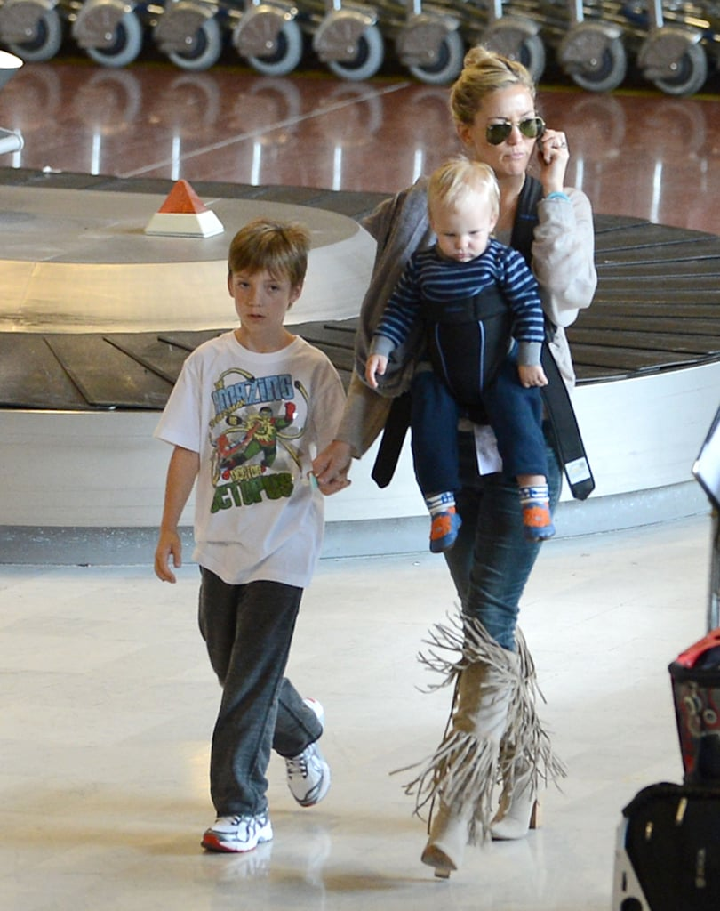 Kate Hudson touched down in Paris with her boys, Ryder and Bingham. The seasoned mama fearlessly sported high-heeled boots while toting little Bing in his carrier.