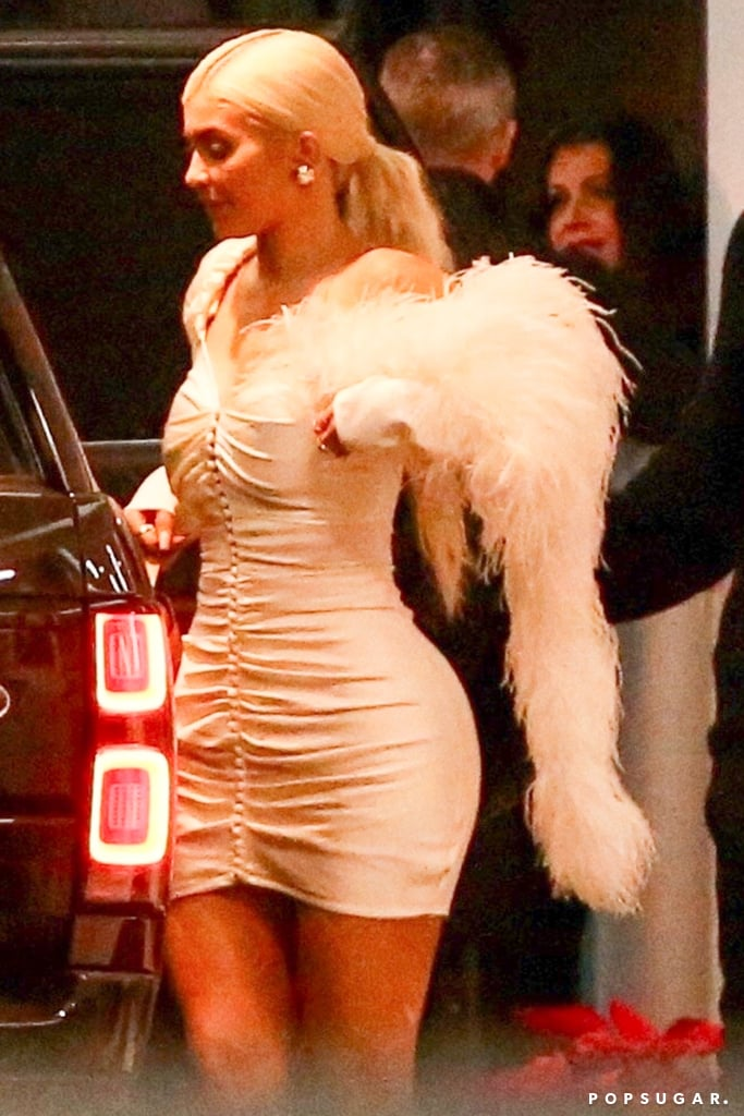 """Kylie Jenner picked the perfect form-fitting dress to ring in the holidays with BFF Jordyn Woods. The 21-year-old reality TV star had a glam night out in Hollywood on Dec. 21, and her skintight Magda Butrym minidress is one for the books.  The off-the-shoulder outfit features romantic detailing, including dramatic ruching, buttons along the center, and draping feathers. She paired the minidress with beige strappy heels and a small gold purse, giving the whole look an angelic vibe. Ahead, see more snaps of her complete look and shop similar dresses for yourself.      Related:                                                                                                           Kylie Jenner's Nostalgic '90s Tee Proves That """"Backstreet's Back, Alright!"""""""