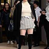 Wearing a beige sweater with a plaid miniskirt and thigh-high boots while in New York in 2019.