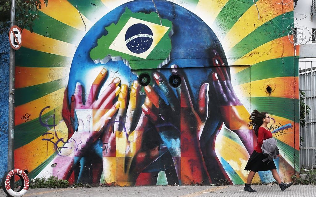 A woman walked past the colorful graffiti wall marked with a Brazilian flag in São Paulo.