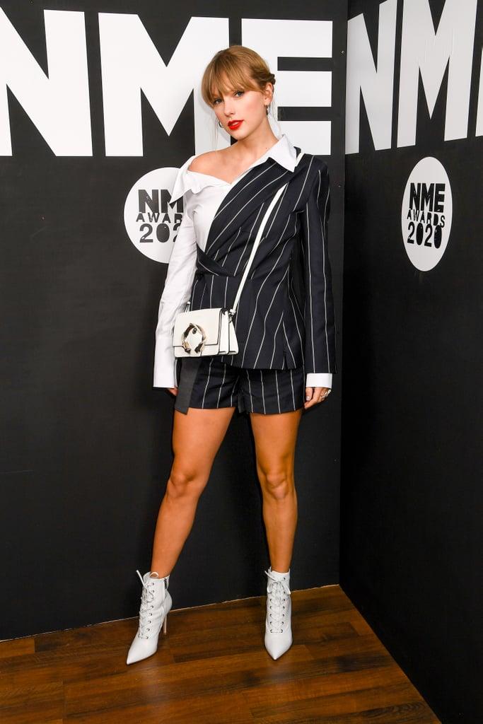 """ظهرت المغنية الأمريكية الشهيرة تايلور سويفت في جوائز NME في لندن يوم أمس الأربعاء بإطلالة أوحت وكأنّها رئيس تنفيذي لشركة أزياء فاخرة بالفعل، ونحن هنا لنطلعكم على كافة تفاصيل إطلالتها الرائعة تلك. حيث تألقت صاحبة أغنية """"Lover"""" هذه ببذلة قصيرة مقلمة باللونين الأبيض والأسود أثناء تسلمها لجائزة """"أفضل ألبوم منفردة في العالم"""" ، وأنا شخصياً أود أن أقدم لها جائزة أفضل إطلالة عملية لعام 2020 حتى الآن. تتضمن الإطلالة، التي تنتمي إلى مجموعة Monse's Resort 2020، قميص أزرار ذو ياقة مقلوبة أعلاه وسترة رسمية ممتزجة فيه مع شورت قصير بدلاً من بنطال البذلات الرسمية التقليدية، ممّا يجعلها أشبه بعمل فنيّ من كونها بذلة رسمية في الحقيقة. كما قرنت تايلور إطلالتها تلك بحقيبة كتف مادلين مذهلة باللون الأبيض والفضي من علامة جيمي تشو (بسعر 1,850$ دولاراً أمريكياً) مع إبزيم على هيئة ثعبان وزوج آسر من أحذية الكاحل الجلدية ذات الأنشوطة من علامة جيانفيتو روسي (بسعر 1,345$ دولاراً أمريكياً). تابعي التصفح أدناه لتأخذي نظرة عن كثب على إطلالة تايلور الأنيقة تلك من مختلف الزوايا."""