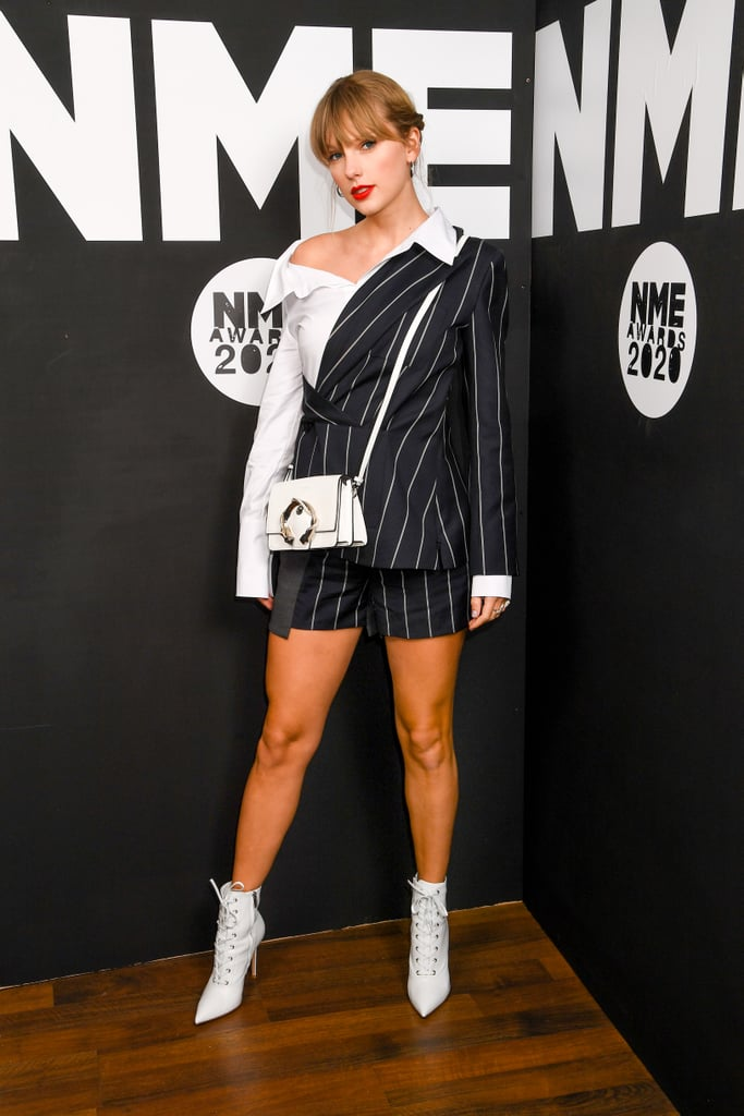"Taylor Swift showed up to the NME Awards in London on Wednesday looking like the CEO of a fashion conglomerate, and we're taking all the style notes. The ""Lover"" singer rocked the pinstriped black and white short suit as she accepted the award for Best Solo Act in the World, and I'm personally tempted to also hand her an award for best business casual look of 2020 so far.  The outfit, from Monse's Resort 2020 collection, featured a collared button-up shirt and blazer mashup jacket and shorts instead of the traditional suit pants, making this look more like a work of art than a suit. Taylor paired the look with a white and silver bedazzled Jimmy Choo Madeline Shoulder Bag ($1,850) with a snake buckle and a cute pair of Gianvito Rossi Lace-Up Leather Ankle Boots ($1,345). Keep scrolling to take a closer look at Taylor's playfully classy look from all angles ahead.       Related:                                                                                                           Marc Jacobs' Runway Had Miley Cyrus, '60s Style, and Diversity We've Been Asking For"