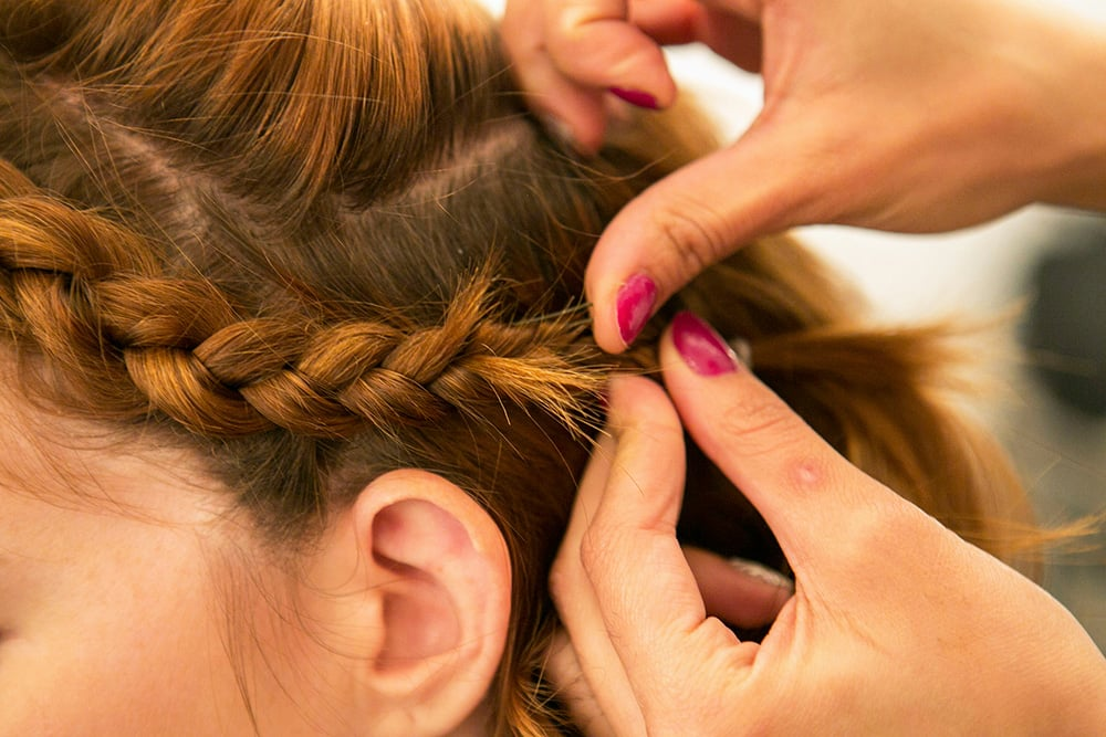 Once you finish curling the middle section, pull back your braid behind your ear and pin it in place using two bobby pins to form an X shape.